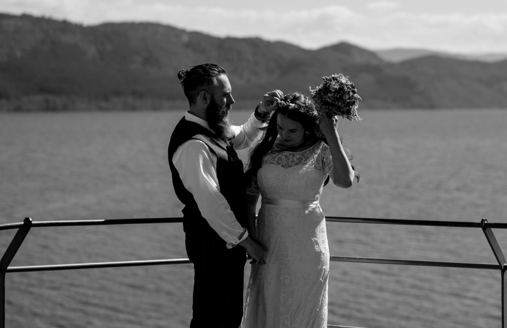 groom helps bride with flower crown